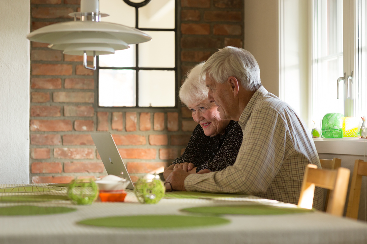 Senior citizens using computer at home.