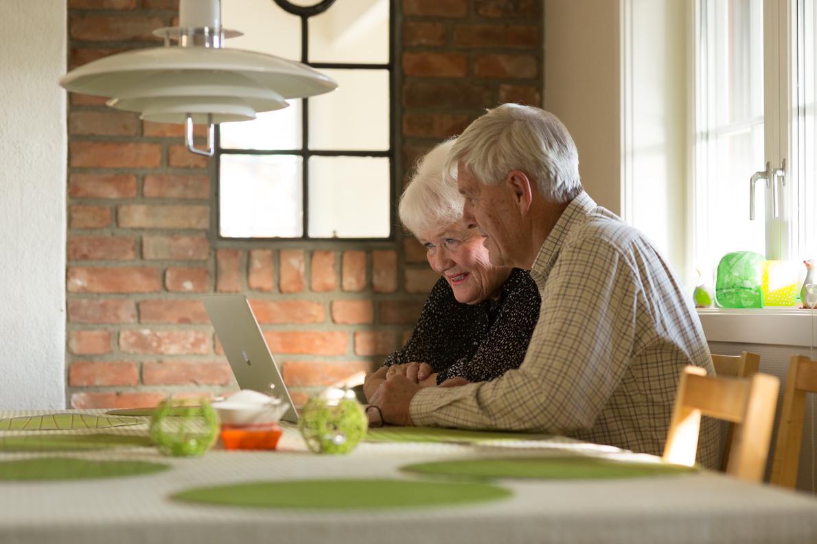 Senior citizens using computer at home.