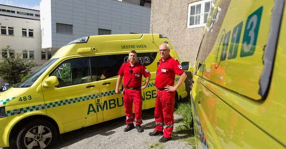 Two ambulance workers standing in front of two ambulances.