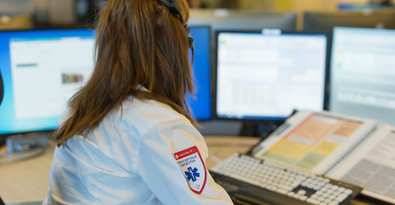 Woman working at emergency medical communication center.