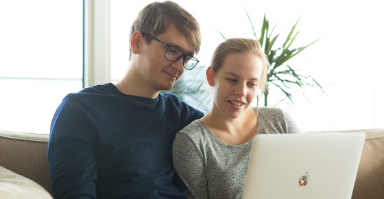 Man and pregnant woman looking at laptop at home.