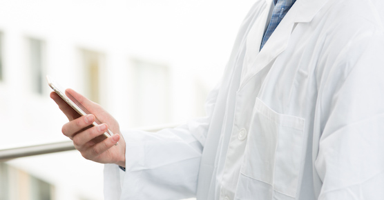 Doctor looking at iPhone.