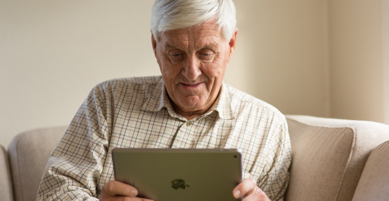 Senior citizen using tablet at home.